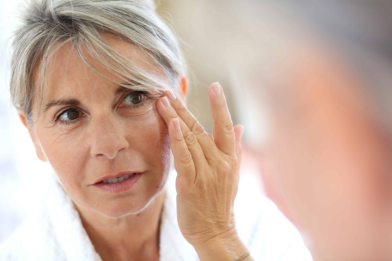 Senior woman applying anti-wrinkles cream